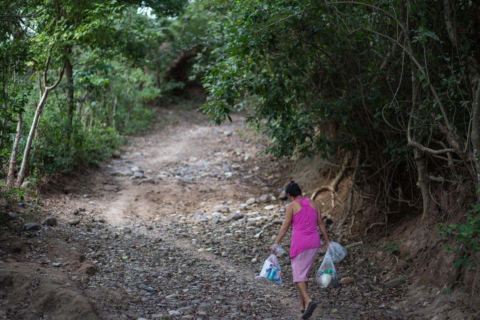 Una mujer regresa a su hogar con dos bolsas de ayuda que el Movimiento Ambientalista Santabarbarense ha llevado hasta la comunidad de la Isla Colina. Santa Bárbara, 25 de enero de 2021. Foto: Martín Cálix.