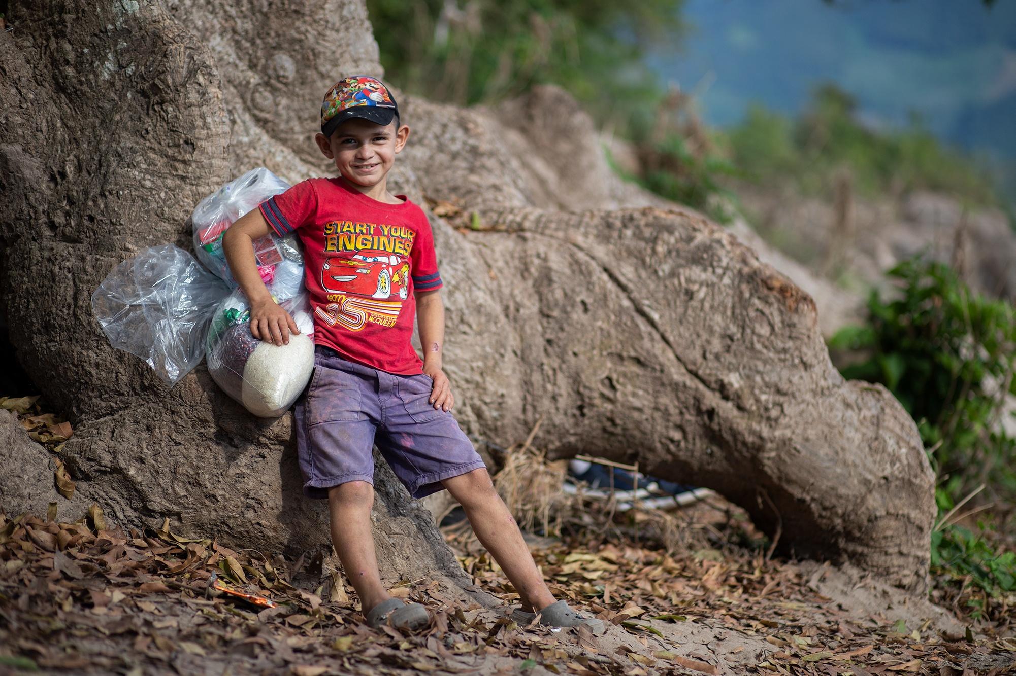 Ángel, de 9 años, debe cargar desde la orilla del río Ulúa hasta su casa, la ayuda alimenticia que el Movimiento Ambientalista Santabarbarense ha gestionado para su comunidad. Santa Bárbara, 25 de enero de 2021. Foto: Martín Cálix.