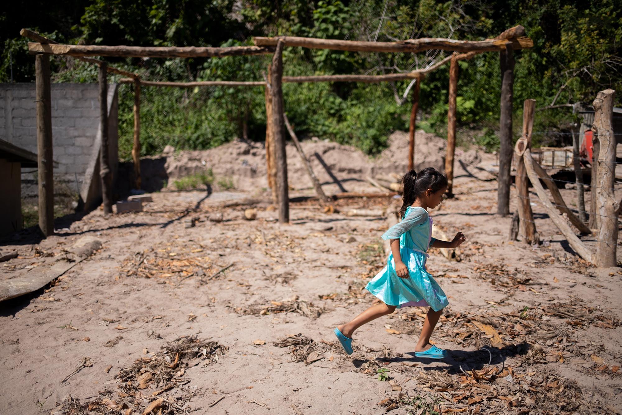 Ashley de 8 años, hija de Mary, corre frente a donde su familia reconstruye su hogar, luego de perderlo soterrado por las inundaciones provocadas por las tormentas Eta e Iota, que provocaron la crecida del río Ulúa a su paso por la comunidad de Brisas del Ulúa. Chinda, Santa Bárbara, 27 de enero de 2021. Foto: Martín Cálix.