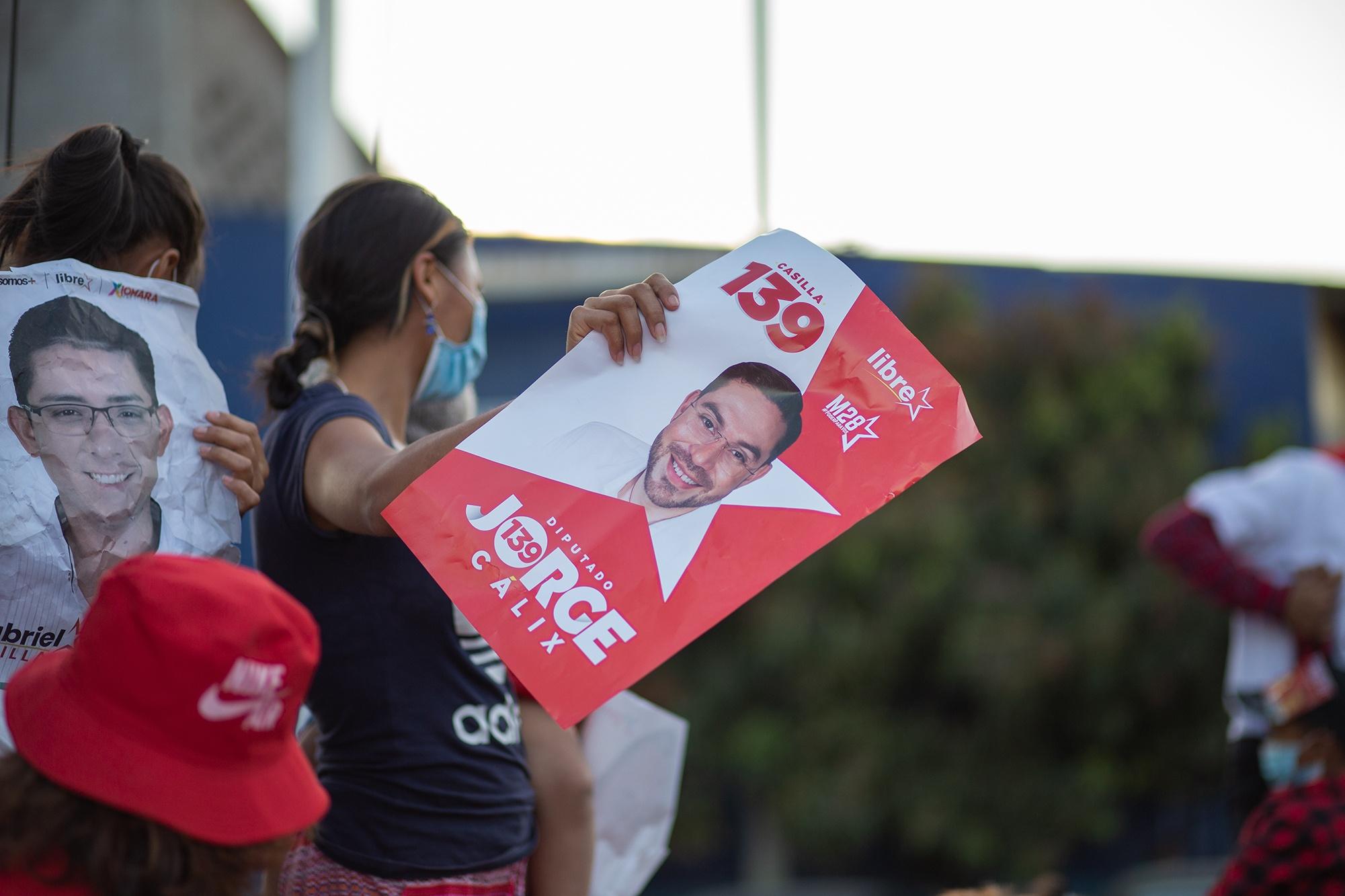Una simpatizante del Partido Libre sostiene un afiche de la precandidatura por el movimiento M28 de Jorge Cálix, actual diputado por Francisco Morazán. Tegucigalpa, 7 de marzo de 2021. Foto: Martín Cálix.