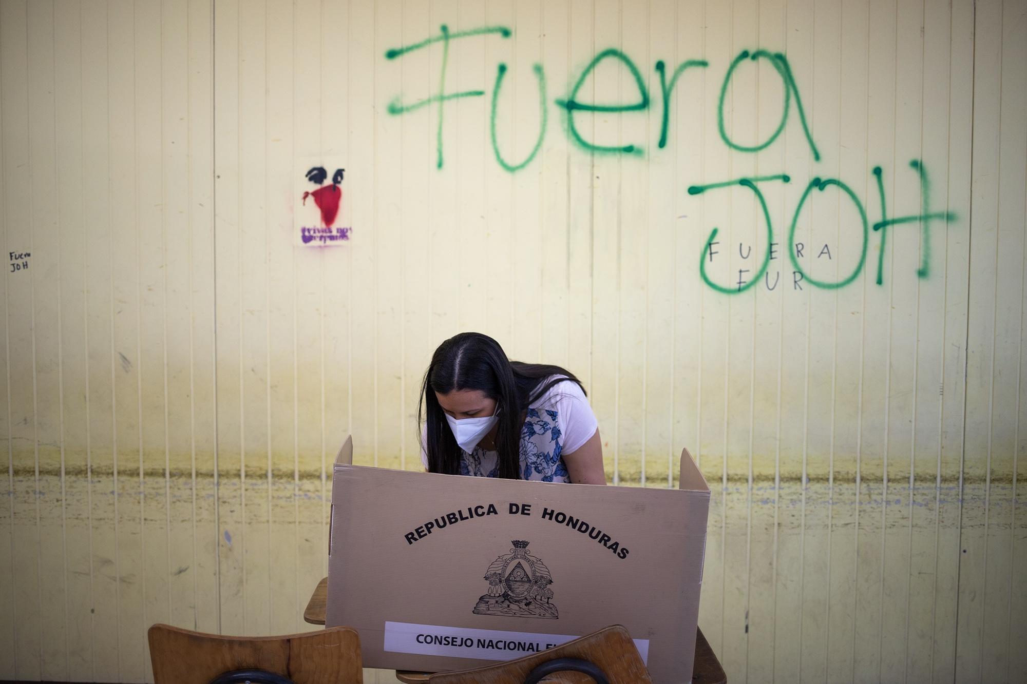 Una simpatizante del Partido Nacional ejerce el sufragio en una mesa electoral colocada delante de una pinta con la leyenda «Fuera JOH» en la Universidad Nacional Autónoma de Honduras. Tegucigalpa, 14 de marzo de 2021. Foto: Martín Cálix.