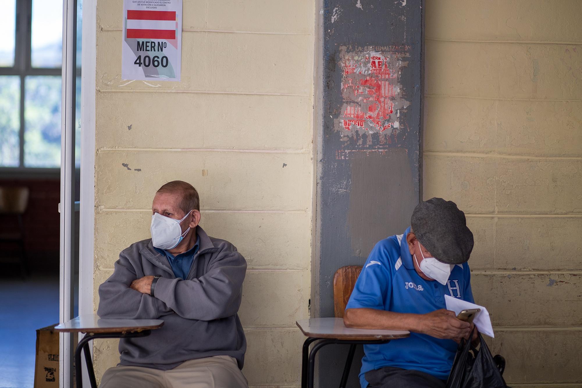 Dos hombres de la tercera edad esperan su turno para ejercer el sufragio en una MER correspondiente al Partido Liberal en el centro de votación de la Universidad Nacional Autónoma de Honduras. Tegucigalpa, 14 de marzo de 2021. Foto: Martín Cálix.