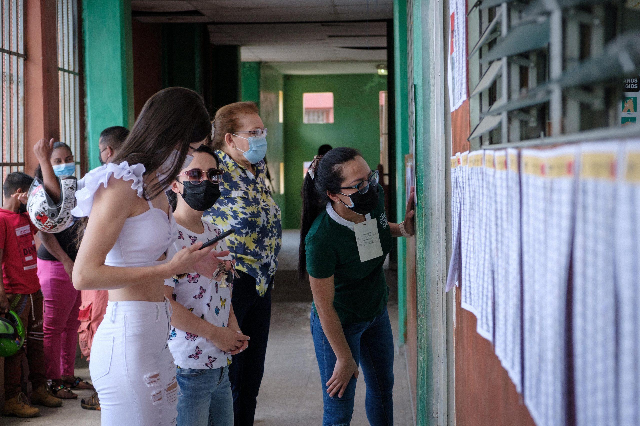 Jóvenes revisan el padrón electoral de una MER en la escuela Presentación Centeno del barrio Cabañas en la ciudad de San Pedro Sula, al final no aparecían en los listados. Varios casos de estos se presentaron en distintos centros de votación a nivel nacional. San Pedro Sula, 14 de marzo de 2021. Foto: Deiby Yanes.
