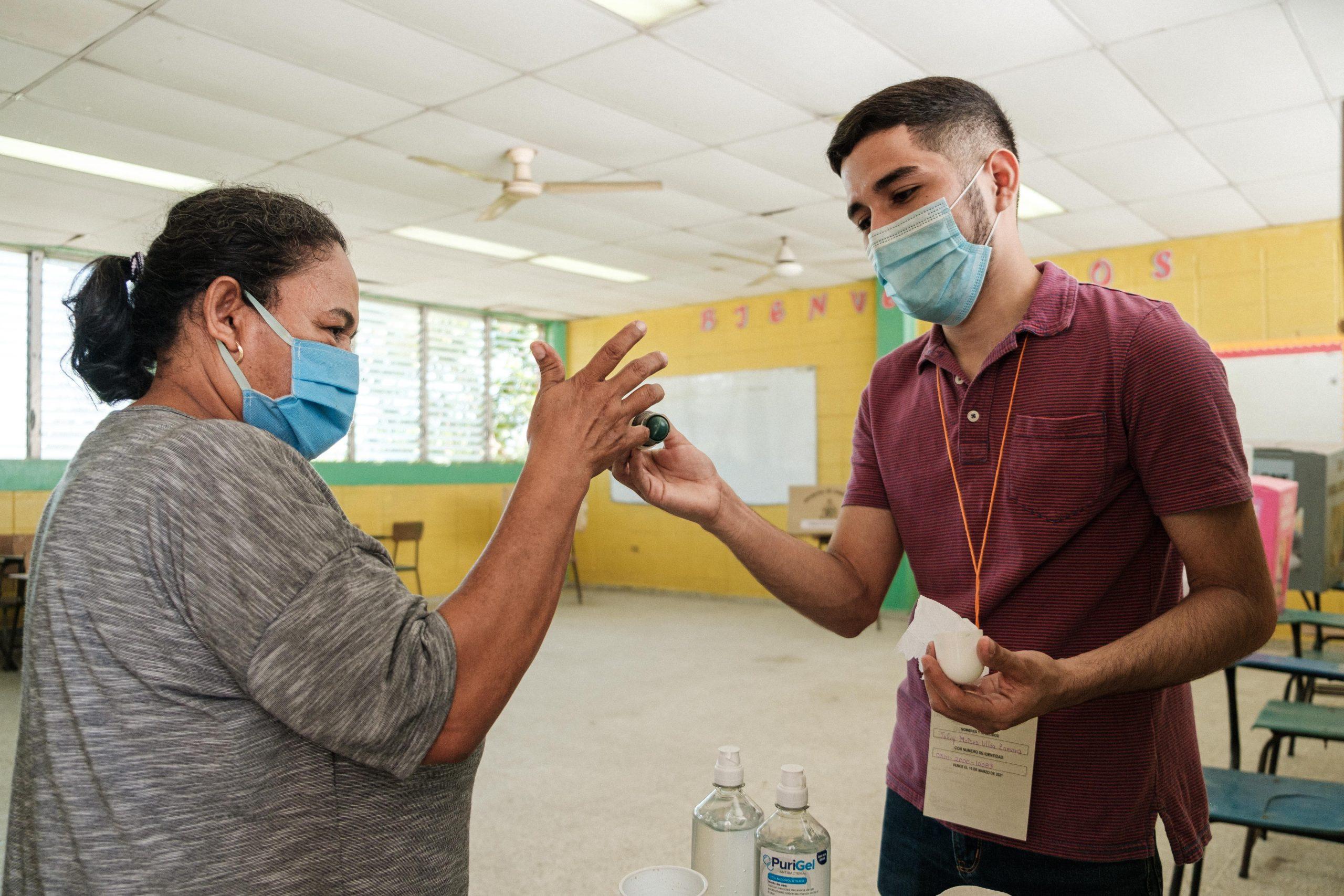 Un miembro de una mesa electoral aplica tinta indeleble en el dedo de una señora que ya ejerció el sufragio. San Pedro Sula, 14 de marzo de 2021. Foto: Deiby Yanes.