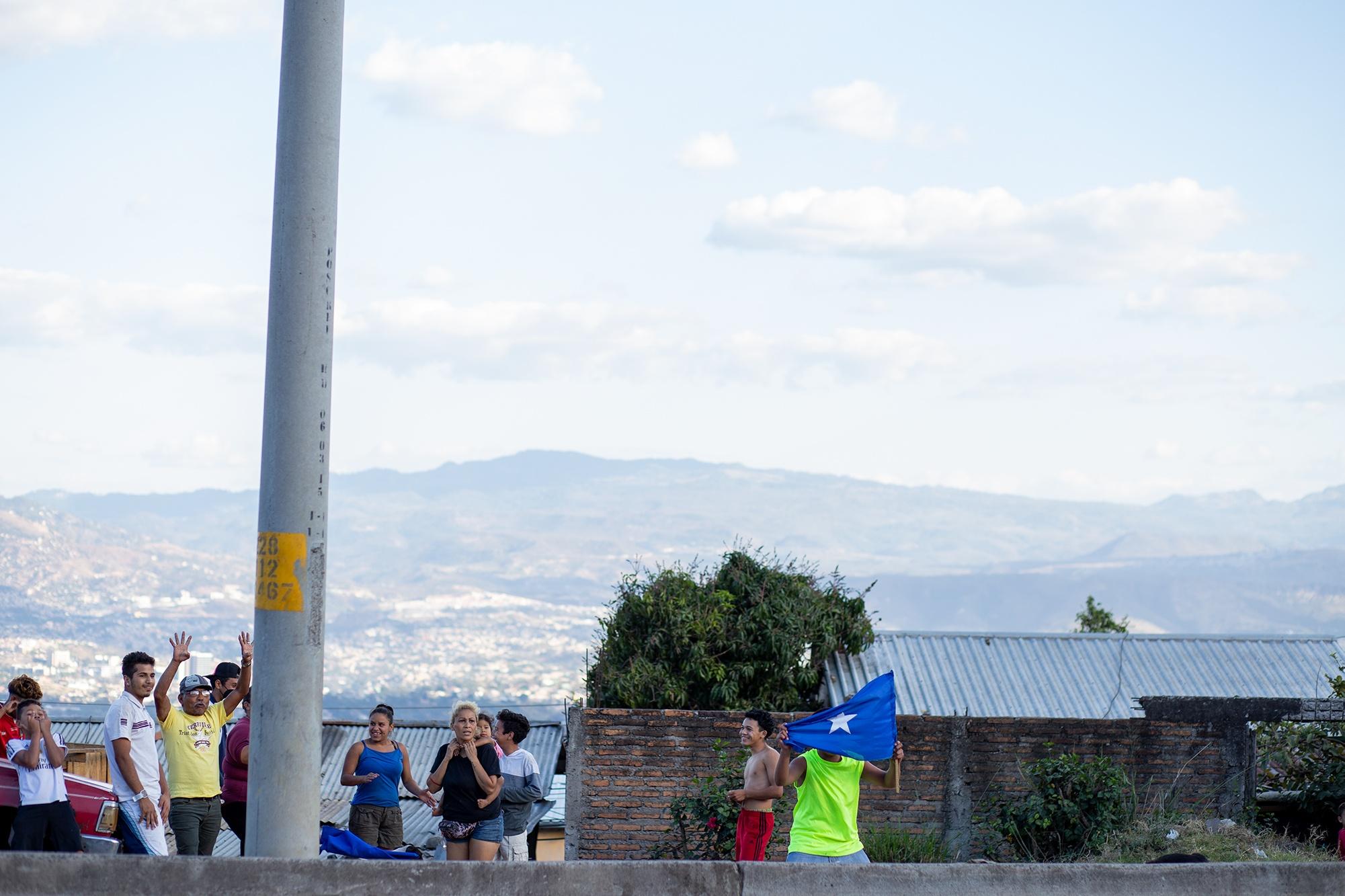 Una familia simpatizante del Partido Nacional de Honduras saca la bandera del partido y todos levantan las manos gritando «cuatro años más» cuando pasa frente a ellos una caravana del Partido Libre. Tegucigalpa, 7 de marzo de 2021. Foto: Martín Cálix.