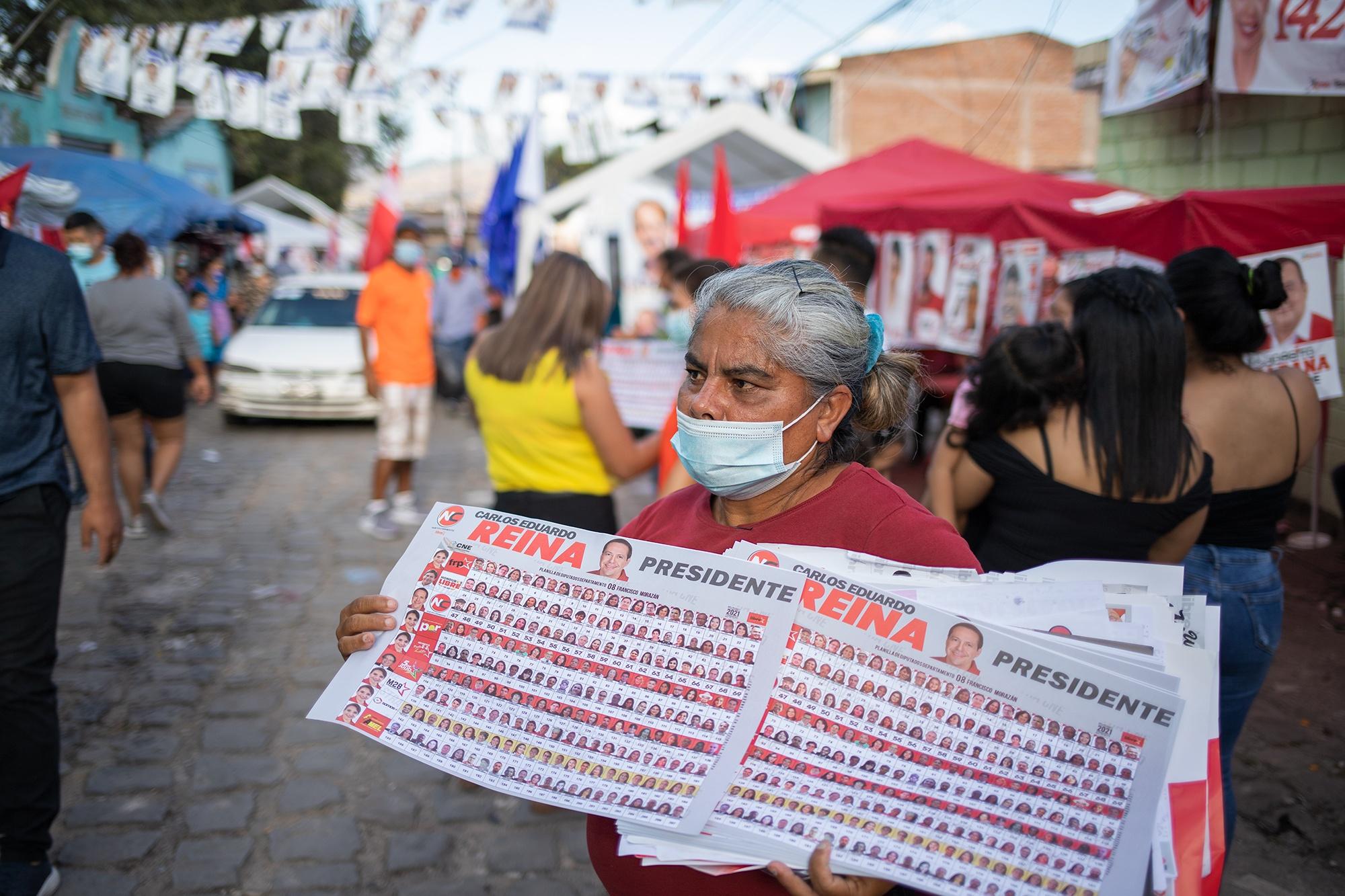 Una mujer entrega boletas electorales del Partido Libre en la Colonia 3 de Mayo, esta colonia suele asociarse con el término de «el cañón azul» por su tradición nacionalista. Comayagüela, 14 de marzo de 2021. Foto: Martín Cálix.