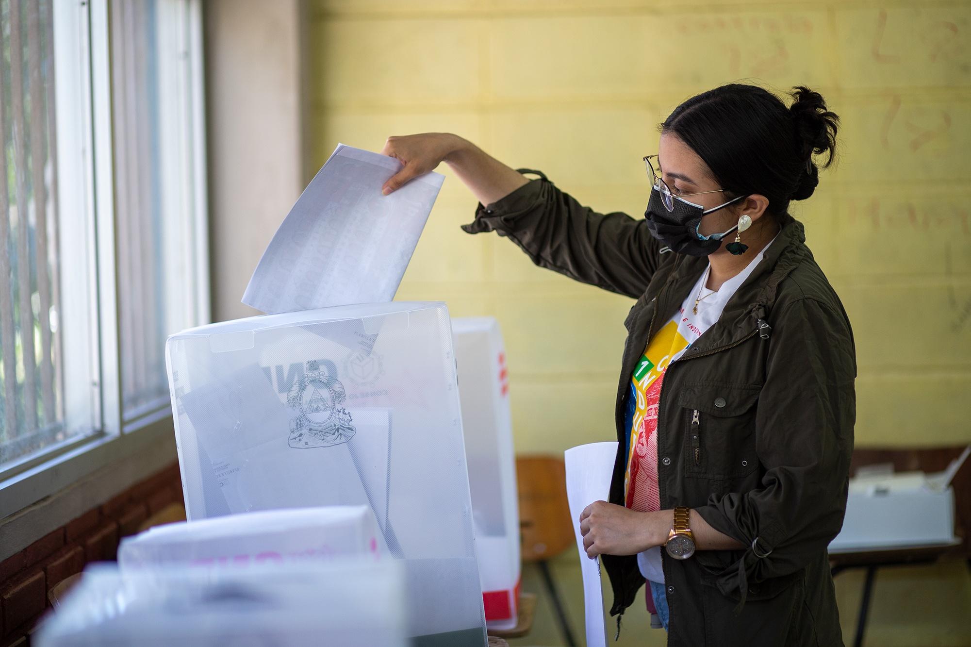 Una joven ejerce el sufragio en una Mesa electoral receptora (MER) en el centro de votación asignado en la Universidad Nacional Autónoma de Honduras. Tegucigalpa, 14 de marzo de 2021. Foto: Martín Cálix.