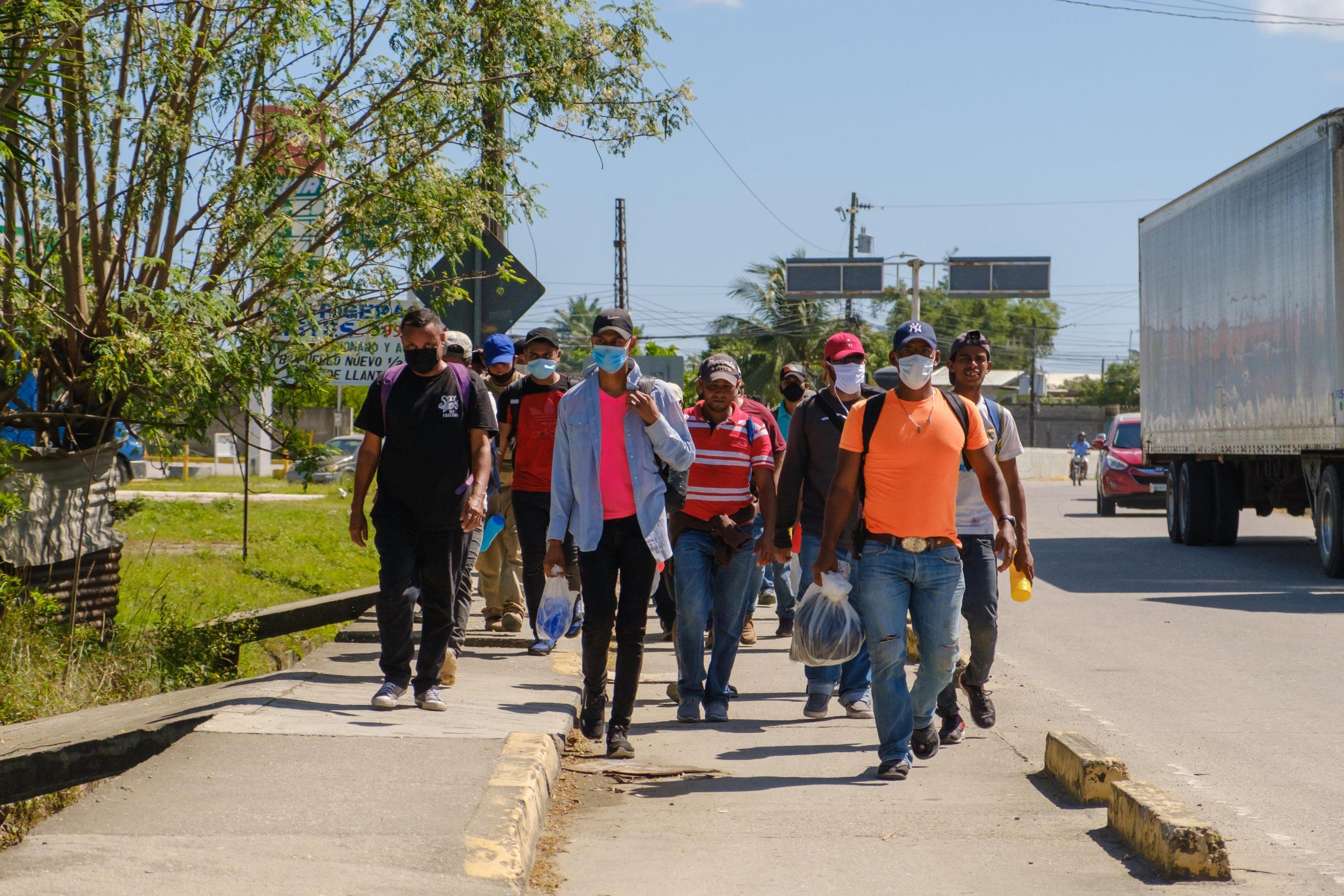 Integrantes de la caravana migrante que salió este 30 de marzo desde SPS, caminan a la altura de Puerto Cortés, en su paso hacia la frontera de Corinto.