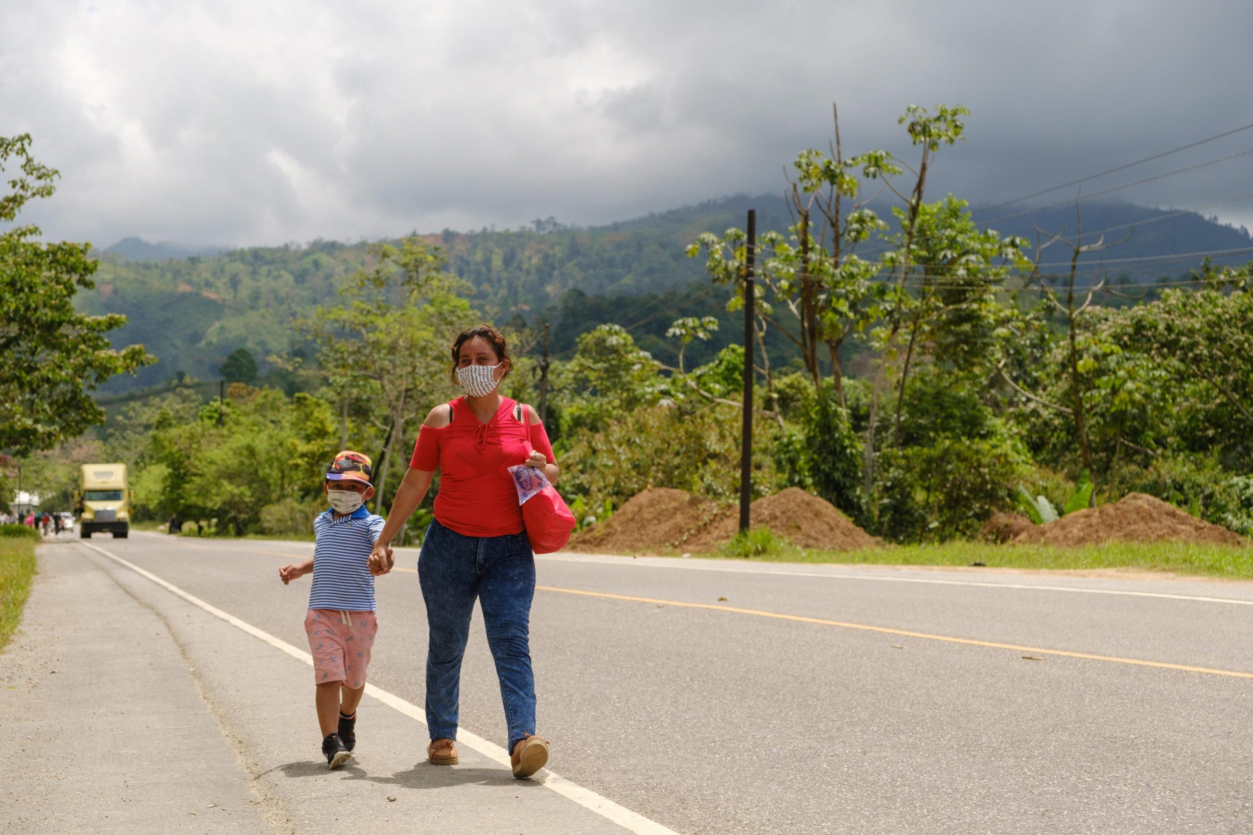 Una mujer camina junto a su hijo, a dos kilómetros antes de llegar a la aduana de Corinto, Frontera con Guatemala.