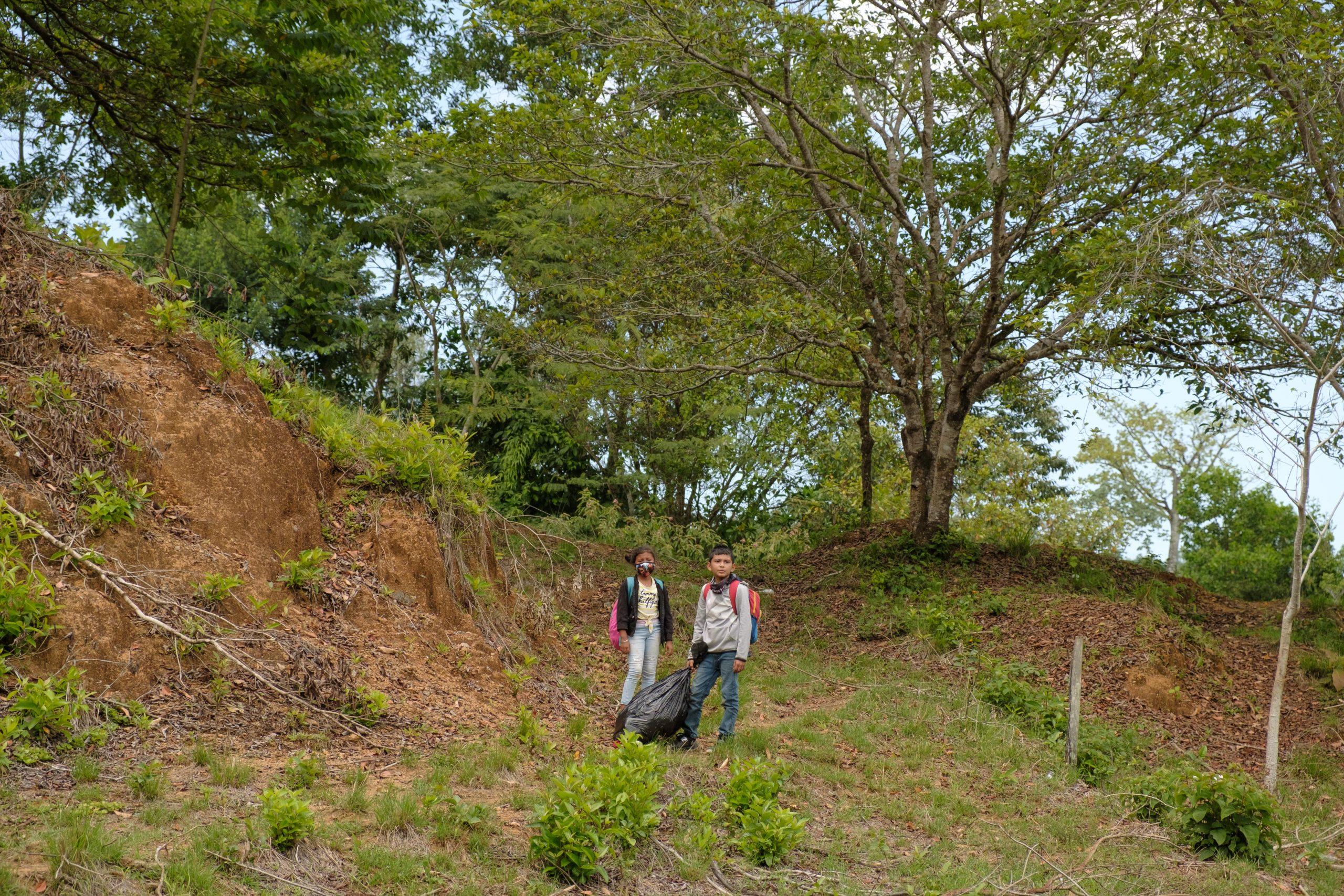 Dos niños esperan a sus padres mientras cruzan por unas colinas en un punto ciego de la frontera para evitar los controles migratorios de la aduana de Corinto entre Honduras y Guatemala.