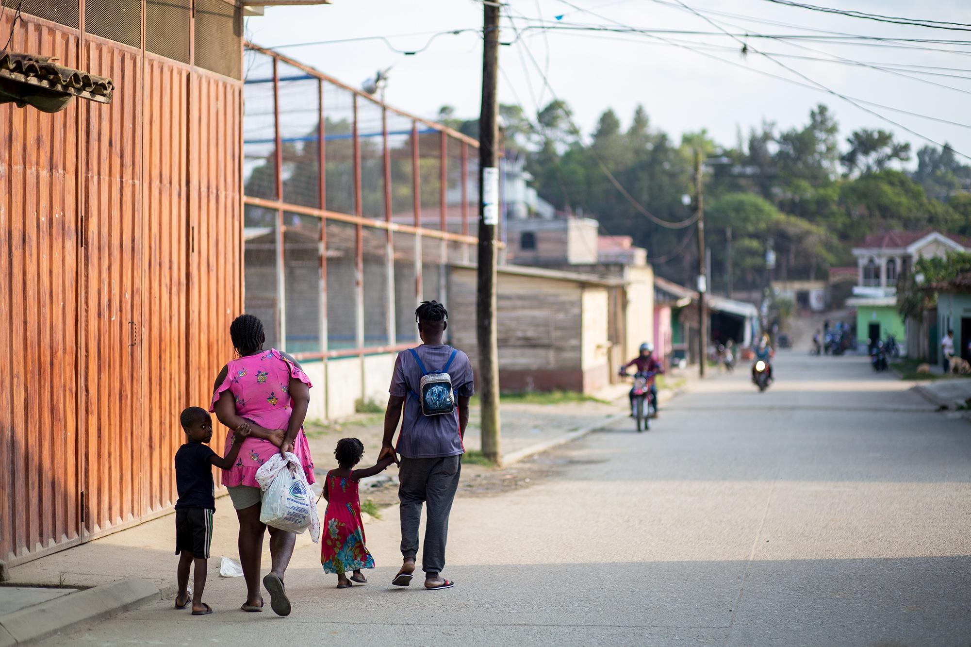 Una familia haitiana camina por una calle del casco urbano de Trójes. Las familias haitianas que han migrado los últimos dos o tres meses desde Chile o Brasil se encuentran con una traba migratoria que impide que continúen con su tránsito hacia Estados Unidos, una multa de 190 dólares por haber cruzado por puntos ciegos hasta territorio hondureño. Trójes, El Paraíso, 20 de abril de 2021. Foto: Martín Cálix.