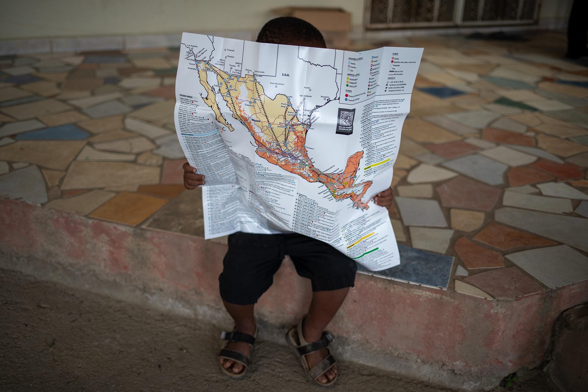Un niño haitiano juega con un mapa que fue donado por Médicos Sin Fronteras, donde se indican los puntos de atención que la organización brinda a lo largo de la ruta migratoria hacia Estados Unidos desde Centroamérica. Trójes, El Paraíso, 21 de abril de 2021. Foto: Martín Cálix.