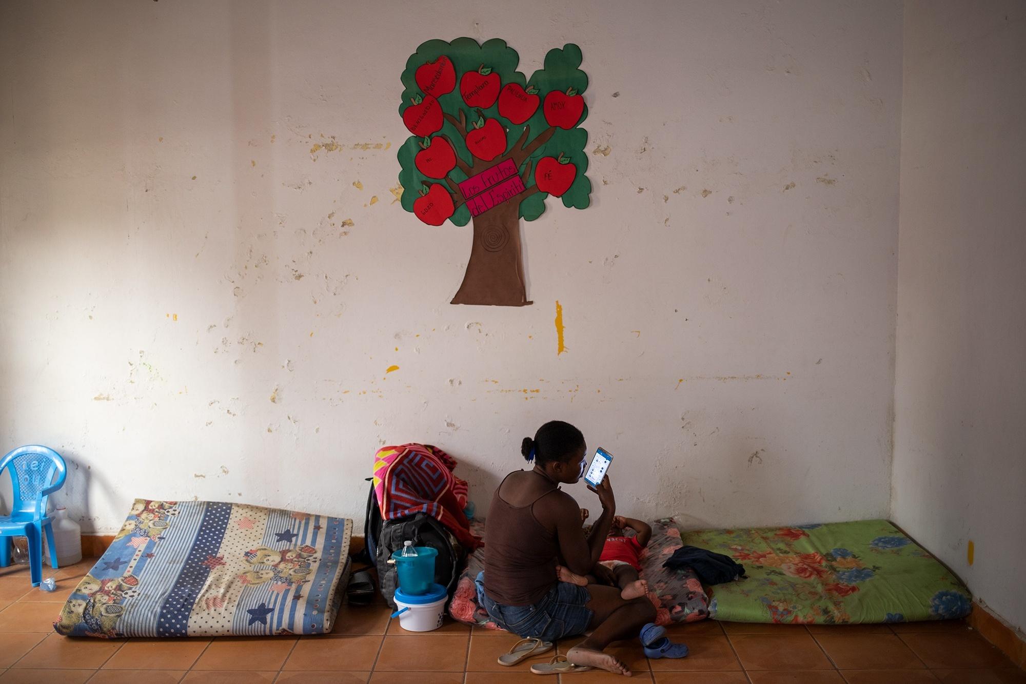Una madre haitiana habla por teléfono mientras cuida a su hijo en la Iglesia Misionera Revelación Divida, la cual ha sido convertida en albergue para las personas migrantes que cruzan la frontera entre Honduras y Nicaragua por puntos ciegos. Trójes, El Paraíso, 21 de abril de 2021. Foto: Martín Cálix.