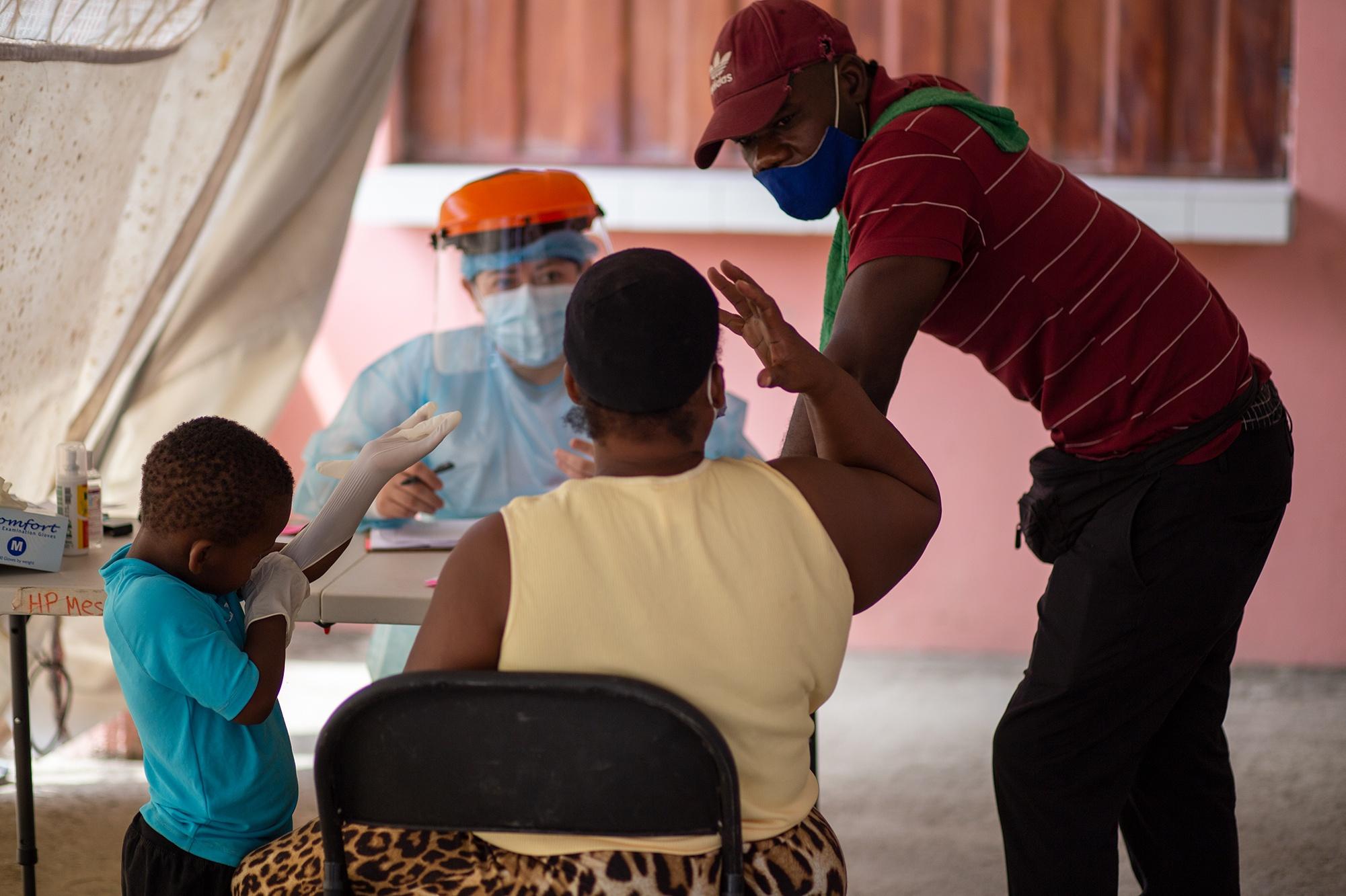 Fontis, de 39 años, ayuda con la traducción a la doctora Marily Fonseca de Médicos Sin Frontera durante la atención médica que da a una madre haitiana y su hijo. Trójes, El Paraíso, 21 de abril de 2021. Foto: Martín Cálix.