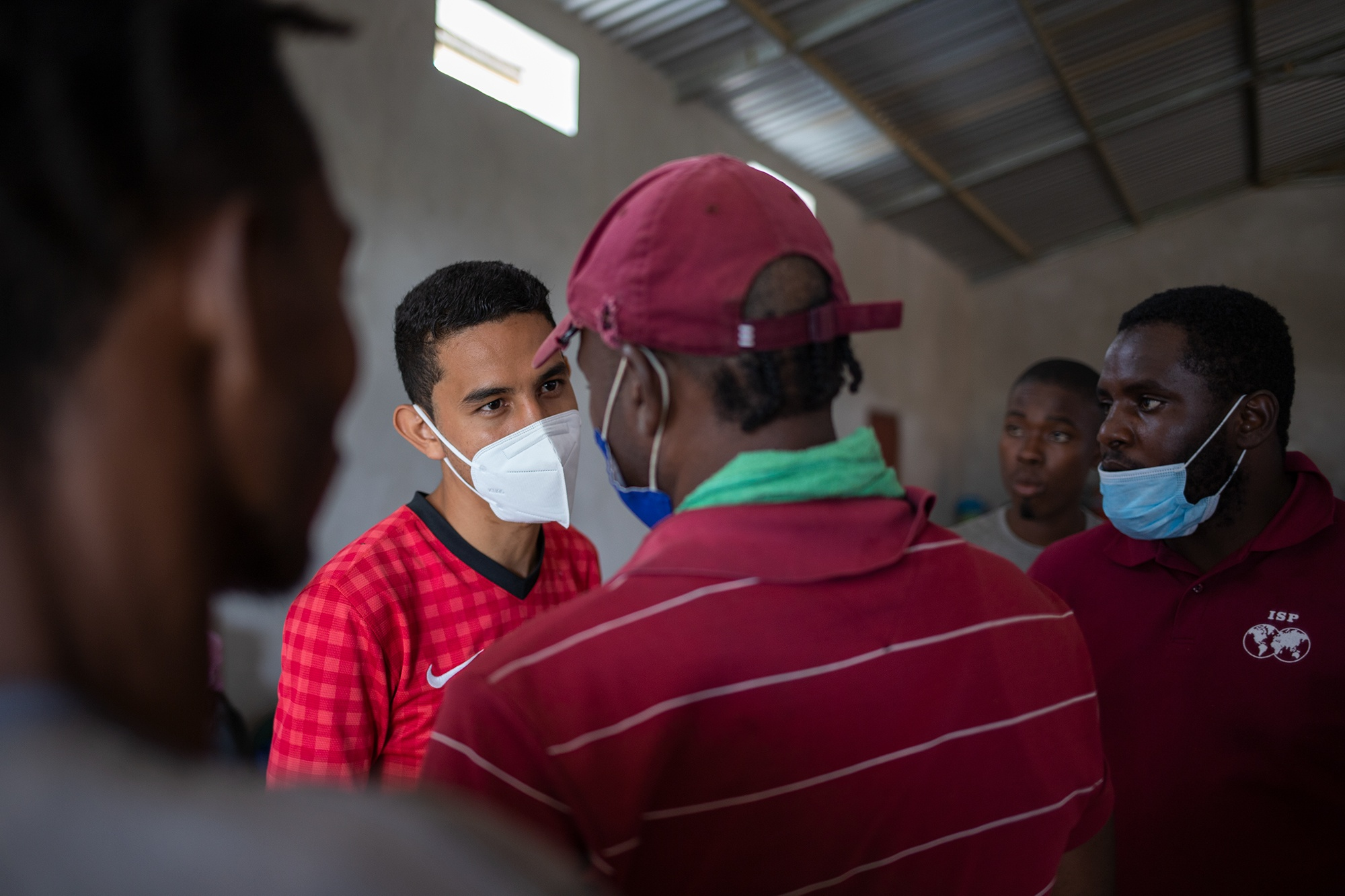 El pastor Kevin Corleto, de 25 años, atiende a un grupo de migrantes durante un recorrido por las iglesias que se han convertido en albergues para los migrantes africanos, haitianos y cubanos que llegan al municipio de Trójes. 22 de abril de 2021. Foto: Martín Cálix.