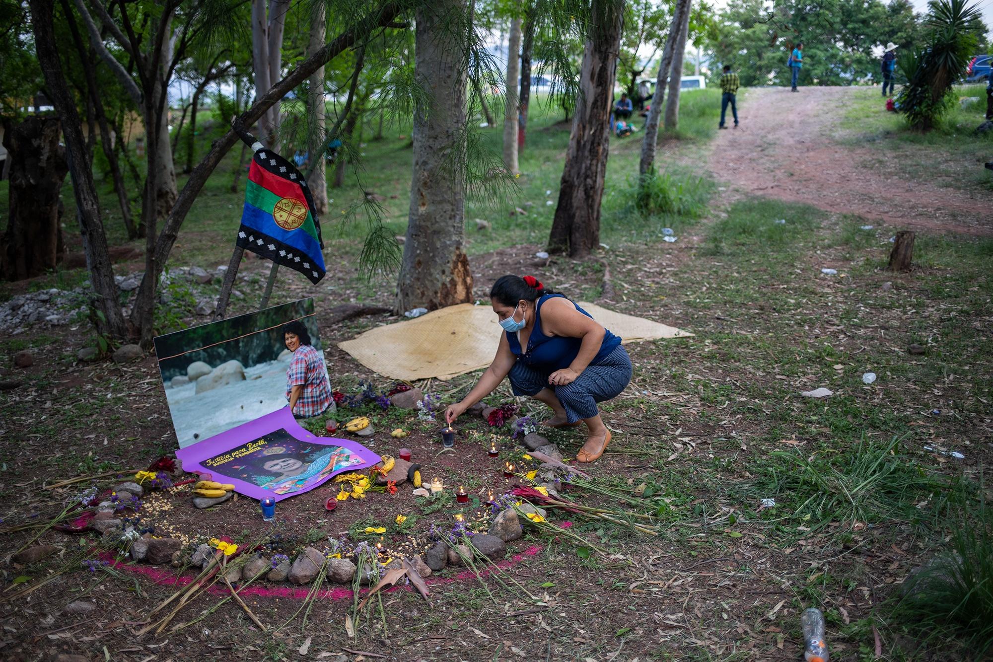 Gabriela Pineda, de la Red de Trabajadoras Domésticas, enciende una veladora en el altar en memoria de Berta Cáceres, ubicado en el centro del Campamento Feminista Viva Berta. Tegucigalpa, 17 de mayo de 2021. Foto: Martín Cálix.