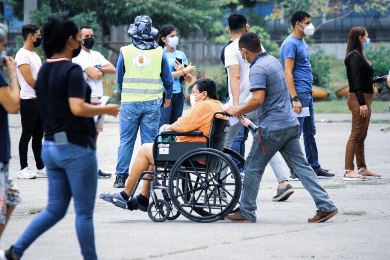 Un hombre en silla de ruedas es apoyado por otro en el parque del Gimnasio Olímpico, que se ha convertido en uno de los centros de vacunación más grandes de San Pedro Sula. Información en el sitio web de la Secretaría de Salud indica que solo un 13% de la población elegible para la vacunación ha recibido la segunda dosis.