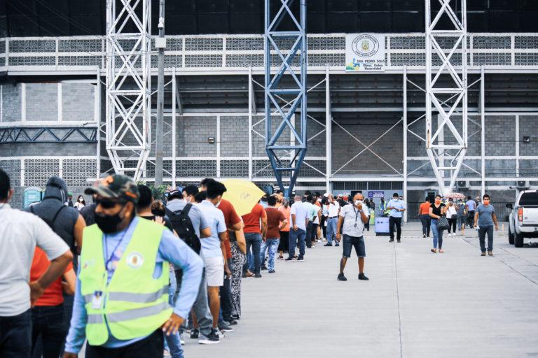 Varias personas  esperan su turno para vacunarse en el Gimnasio Olímpico Metropolitano. La inmunización es una de las herramientas para frenar el contagio de COVID. En Cortés, la positividad de las pruebas realizadas ronda el 64%.