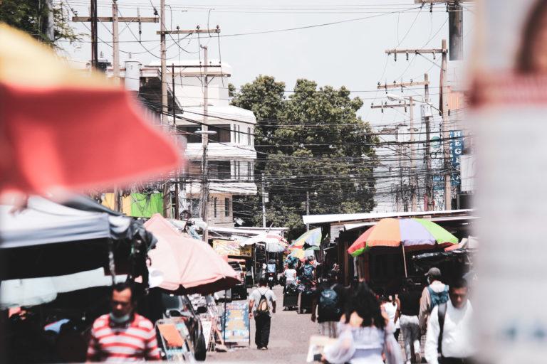 Dos hombres caminan sin preocupación y sin mascarilla en la segunda calle del barrio El Centro en San Pedro Sula, una de las más concurridas y que ha sido ocupada por el mercado informal.