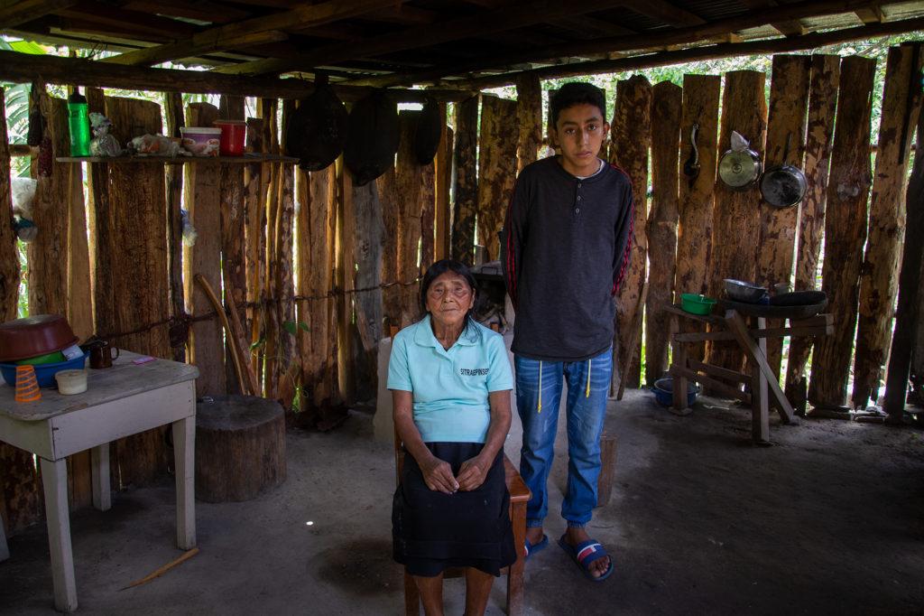 En la cocina de su hogar, son retratados Felicita y su nieto. Felicita se hizo cargo de su nieto cuando su hija y madre del joven murió. En la actualidad dependen de la ayuda que otra de sus hijas que vive en Tegucigalpa —y suspendida de su trabajo durante la pandemia— pueda hacerle llegar. Opatoro, 8 de agosto de 2020. Foto: Martín Cálix
