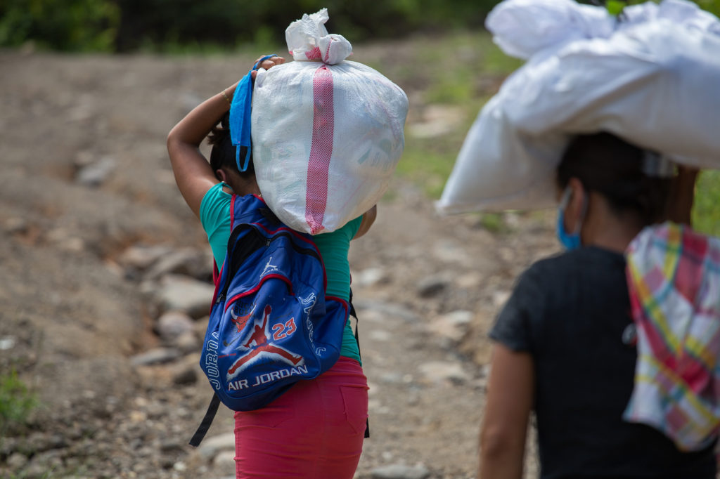 Dos mujeres que se han dividido la carga, caminan de regreso a sus hogares, ubicados al menos a una hora desde el punto de entrega. Esta ayuda —aunque mínima— ayudará a que sus familias se alimenten al menos 15 días. Aguanqueterique, La Paz, 29 de agosto de 2020. Foto: Martín Cálix