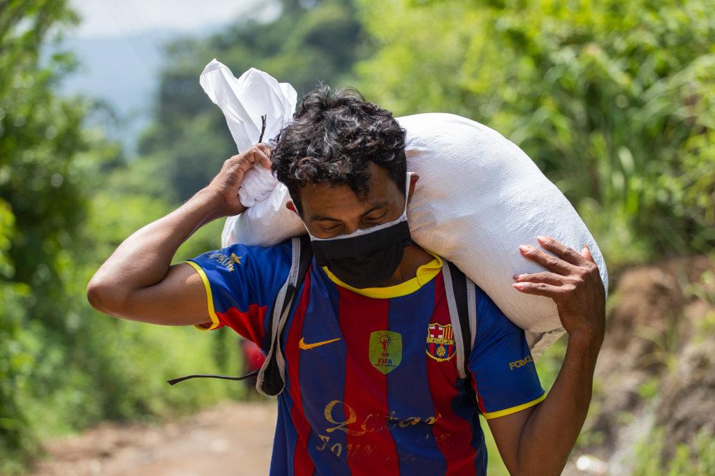 Un joven carga con el saco de alimentos entregado por la Cruz Roja, para llegar a su comunidad este joven al menos deberá caminar media hora con el saco en sus espaldas. Curarén, Francisco Morazán, 27 de agosto de 2020. Foto: Martín Cálix