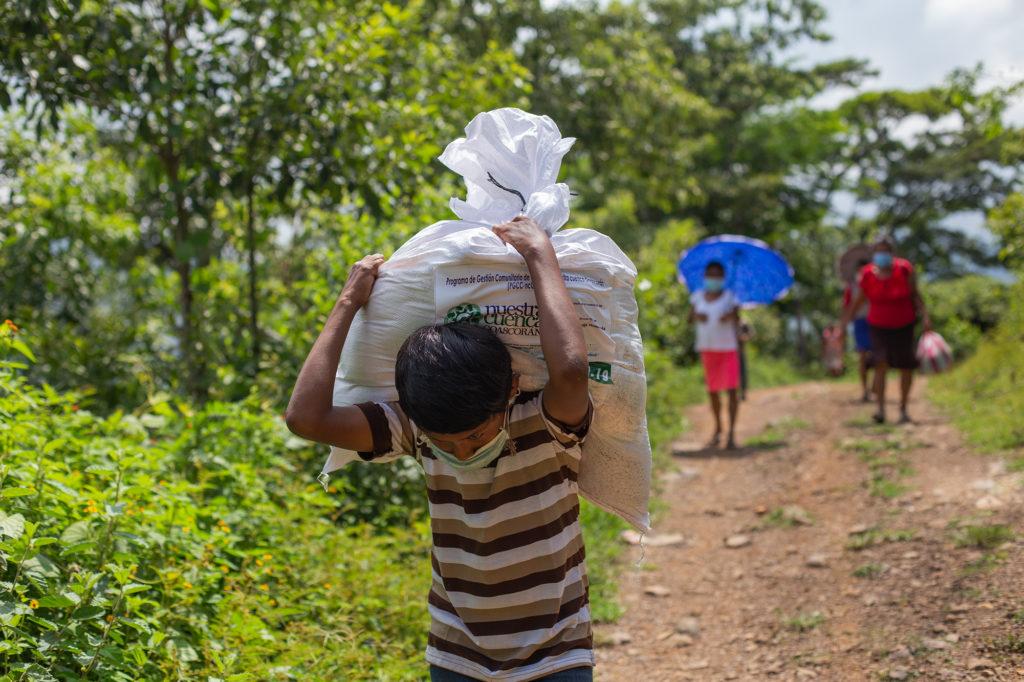 Un niño carga con el saco de alimentos entregado por la Cruz Roja Hondureña a su familia, caminará con él al menos media hora hasta su casa. Curarén, Francisco Morazán, 27 de agosto de 2020. Foto: Martín Cálix