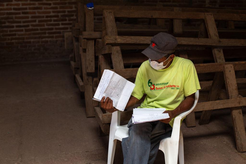 Un líder comunitario revisa el listado de personas a beneficiar en el proyecto de entrega de alimentos que coordina la Cruz Roja. Opatoro, La Paz, 8 de agosto de 2020. Foto: Martín Cálix